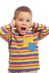 Little boy closing ears with his hands